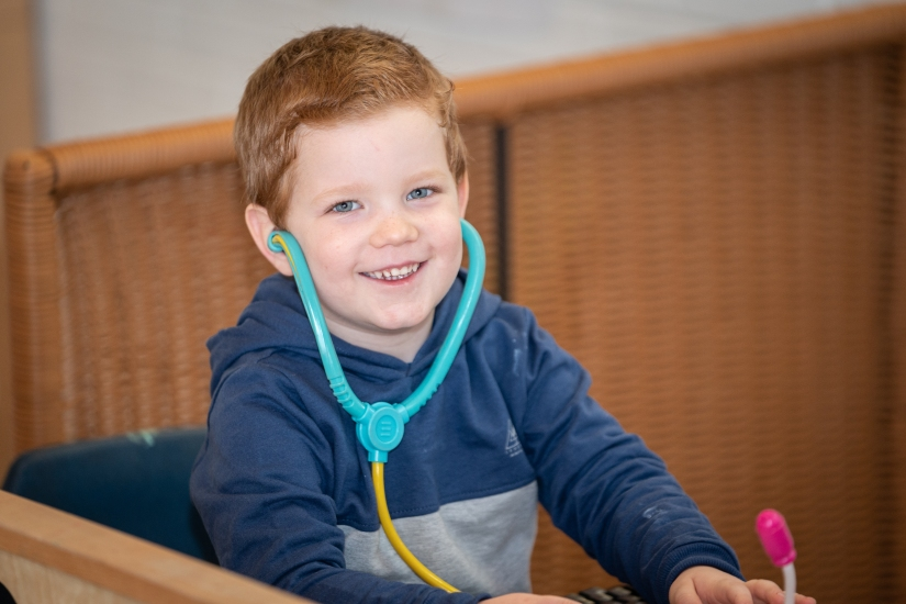 Smiling child plays with a stethoscope at PolkaDots Cresswood Nursery
