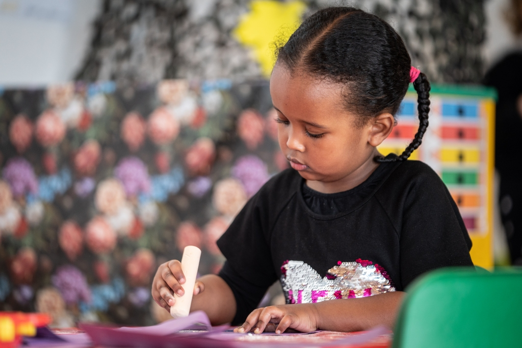 A child concentrating while drawing at PolkaDots Nursery
