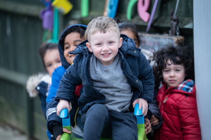 Children play outside on a slide at PolkaDots Cresswood Nursery